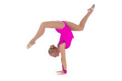 Gymnast in a costume doing stretching exercise. Smiling flexible girl gymnast in a costume doing stretching exercise over white background stock photo