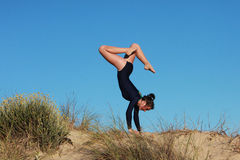 Gymnast doing acrobatic handstand on the beach Stock Photo