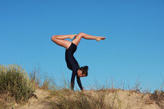 Gymnast doing acrobatic handstand on the beach Royalty Free Stock Photography
