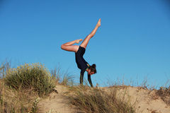 Gymnast doing acrobatic handstand on the beach Stock Images