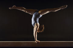 Gymnast Doing Split Handstand On Balance Beam. Side view of a female gymnast doing split handstand on balance beam against black background Stock Photos