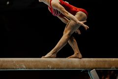 Gymnast för övningsbalansbomkvinnlig arkivfoto
