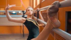 Gymnast för ung kvinna som gör sträcka benet på barren i en studio royaltyfri foto