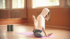 Gymnast för ung kvinna som värmer sammanträde på golvet upp och gör övningar på hennes ben - sträcka lager videofilmer