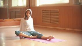 Gymnast för ung kvinna som värmer sammanträde på golvet upp och gör benövningar stock video