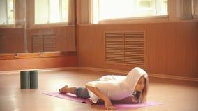 Gymnast för ung kvinna som värmer sammanträde på golvet upp och gör sträcka övningar lager videofilmer