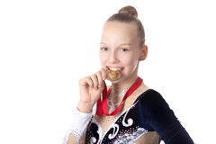 Gymnast girl biting her award medal. Portrait of beautiful happy smiling cool fit gymnast or skater young woman in sportswear dress posing, jokingly biting Royalty Free Stock Photos