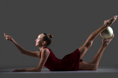 Gymnast girl doing backbend exercise with ball Stock Photography