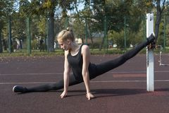 Gymnast girl doing splits on the athletic field in a park stock photo