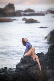 Gymnast girl sitting on a stone Stock Image