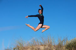 Gymnast jumping joyfully on the beach Royalty Free Stock Image