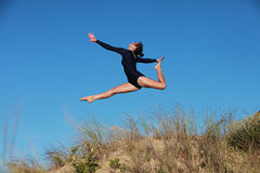 Gymnast jumping joyfully on the beach Stock Photo