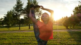 Gymnast lifts a leg in a vertical twine in a city park on sunset, camera movement royalty free stock photos