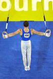Gymnast rings 001. A male gymnast prefoms a routine on the rings during competition Stock Photos