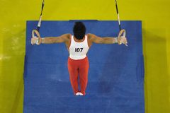 Gymnast rings 004. A male gymnast preforms a routine on the rings during competition Royalty Free Stock Photography