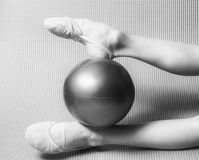Gymnast's feet in toe shoes with ball. Gymnast's feet in toe shoes with red ball royalty free stock photos