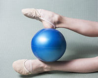 Gymnast's feet in toe shoes with ball. Gymnast's feet in toe shoes with red ball stock image