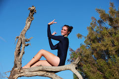 Gymnast sitting in a dead tree Royalty Free Stock Images