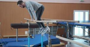 Gymnast som gör genomkörare på barr på idrottshallen stock video
