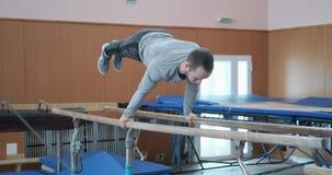 Gymnast som gör plancheövning på barr stock video