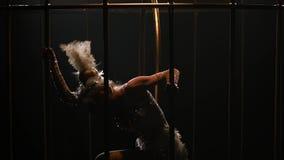 Gymnast a som rotera på ett beslag i en guld- bur Svart bakgrund långsam rörelse close upp lager videofilmer