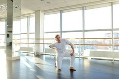 Gymnast in sportswear training near ballet barre in sport gym. Gymnast train near ballet barre in sport gym, guy diligently doing stretching exercises for legs Stock Images