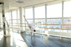 Gymnast in sportswear training near ballet barre in sport gym. Gymnast train near ballet barre in sport gym, guy diligently doing stretching exercises for legs Royalty Free Stock Photos