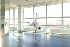 Gymnast in sportswear training near ballet barre in sport gym. Gymnast train near ballet barre in sport gym, guy diligently doing stretching exercises for legs Stock Photography
