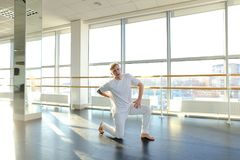 Gymnast in sportswear training near ballet barre in sport gym. Gymnast train near ballet barre in sport gym, guy diligently doing stretching exercises for legs Stock Image