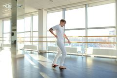 Gymnast in sportswear training near ballet barre in sport gym. Gymnast train near ballet barre in sport gym, guy diligently doing stretching exercises for legs Stock Photos