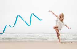 Gymnast woman dance with ribbon on the beach Royalty Free Stock Photos