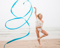 Gymnast woman dance with ribbon on the beach Stock Photos