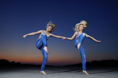 Gymnast women jump at night Royalty Free Stock Photography