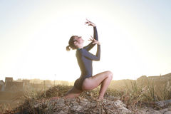 Gymnast worshipping with sun behind her Stock Image