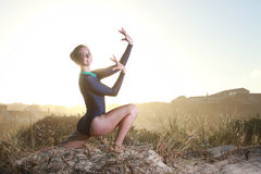 Gymnast worshipping with sun behind her Stock Photography