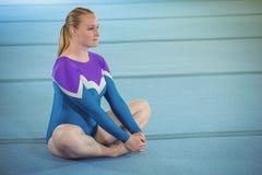 Gymnaste féminin exécutant étirant l'exercice photos stock