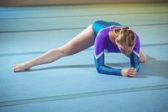 Gymnaste féminin exécutant étirant l'exercice photographie stock libre de droits