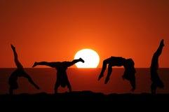 Gymnaste féminin sur la plage dans le coucher du soleil Photographie stock libre de droits