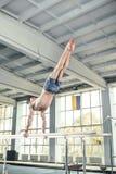 Gymnaste masculin exécutant l'appui renversé sur des barres parallèles Photos stock