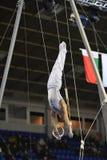 Gymnaste masculin exécutant sur les anneaux gymnastiques stationnaires Image stock