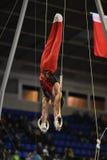 Gymnaste masculin exécutant sur les anneaux gymnastiques stationnaires Images libres de droits