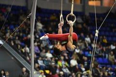 Gymnaste masculin exécutant sur les anneaux gymnastiques stationnaires Photographie stock libre de droits