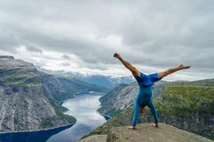 Gymnaste se tenant sur ses mains sur le bord avec le fjord sur le fond près de Trolltunga norway image libre de droits