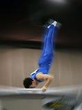 Gymnaste sur le bar parallèle photo stock