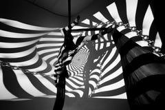 Gymnasten gör övningen mot bakgrunden av de svarta stängerna Arkivfoton