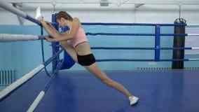 Gymnasten med böjliga ben gör sträckning under genomkörare för konkurrens i sportstudio lager videofilmer