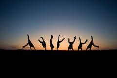 Gymnastes silhouettés dans le coucher du soleil Photo stock