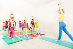 Gymnastic coach teaching kids stretching hands Royalty Free Stock Photo