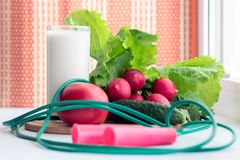 Gymnastic jump rope and vegetables for a healthy diet - tomato, cucumber, radish and lettuce are on the table near the window. A stock photos