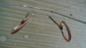 Gymnastic rings are suspended to an iron arch, rings for training in the hall. Bottom view stock video footage